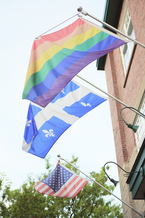 gay pride flag: A gay pride flag hanging from a building Quebec Stock Photo