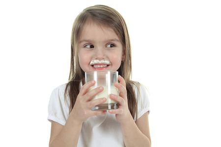 8   9 years: Little girl drinking milk on white background. Studio shot