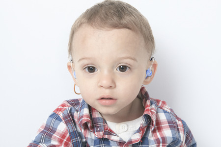 A boy with a hearing aids on gray background