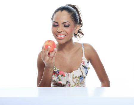 portrait of mulatto smiling woman isolated on white studio shot eating peach photo