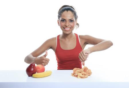 bad banana: beautiful young woman choosing between apple and potato chips Stock Photo