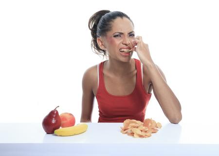 dudando: hermosa mujer joven que elige entre la manzana y papas fritas