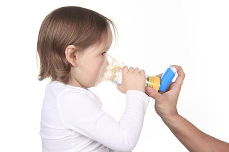inhalator: A mother giving in inhalator to a little girl