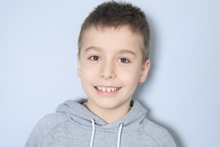 ead: Portrait of a boy in front of a gray background