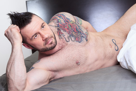 A sexy naked man lay in the bed