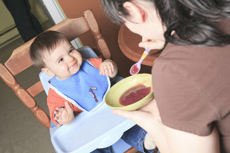 12 15 months: Mother feed baby in the kitchen with spoon. Stock Photo