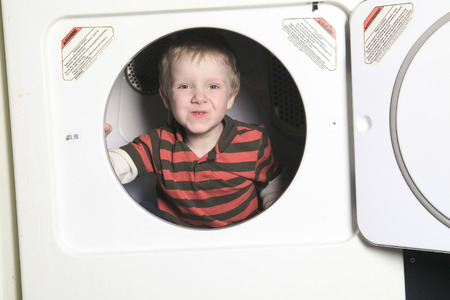 A kid on the dryer having fun