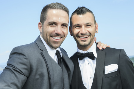 relaxed man: Portrait of a loving gay male couple on their wedding day. Stock Photo