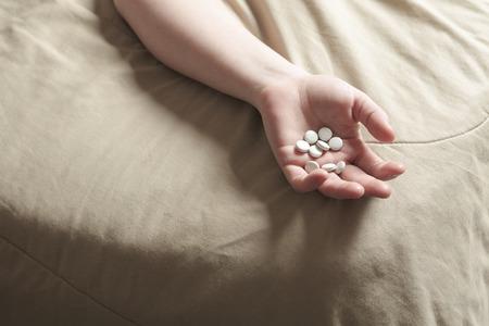 A sad woman taking medication on bed. Фото со стока
