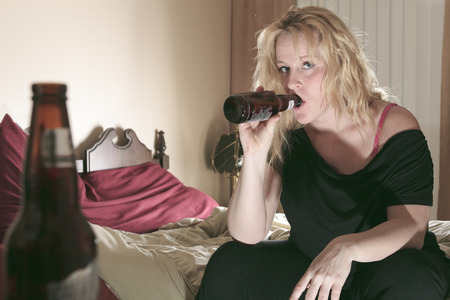 messy room: A alcoholic woman drinking beer in his bedroom.