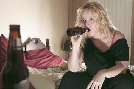 Een alcoholische vrouw het drinken bier in zijn slaapkamer.