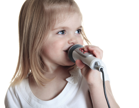 songster: Funny little girl singing with a microphone isolated on white background