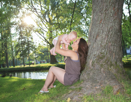25 to 30 years old: A mother with is baby on a beautiful forest