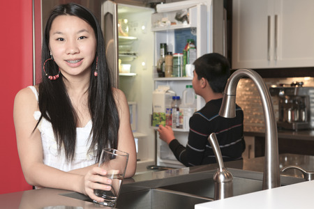 fridge: A teenager girl drinking water in the kitchen Stock Photo
