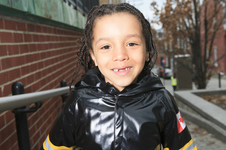An african child in the playground of a shool with raincoat 新聞圖片