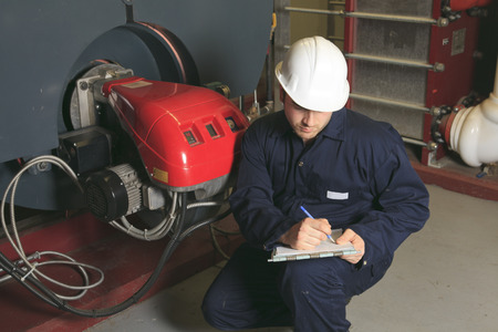 A maintenance engineer checking technical data of heating system equipment in a boiler room Stock Photo