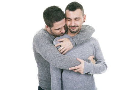 hombres jovenes: Una pareja homosexual en un fondo blanco en el estudio