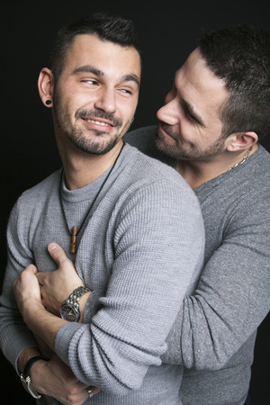 clasped hands: A gay couple on black studio