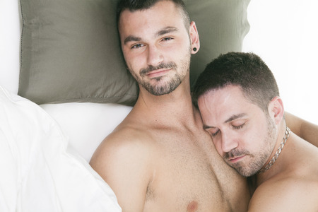 french kiss: A homosexual couple onder a bed in studio white on studio. Stock Photo