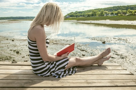 personas leyendo: Un retrato de la muchacha en el lado de un mar Foto de archivo