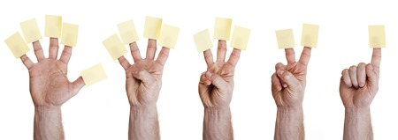 sticky hands: five hands holding sticky note on finger over white background