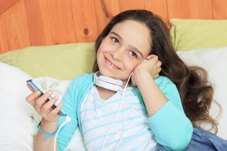 A children girl listening music lay on his bed Reklamní fotografie