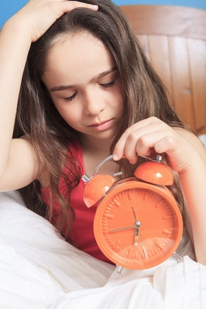 oversleep: An unhappy girl waking up with clock on his hand Stock Photo