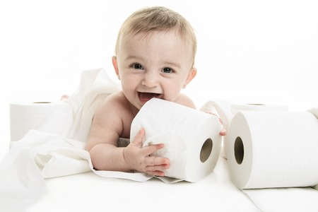 A Toddler ripping up toilet paper in bathroom studio