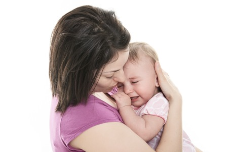 sad cute baby: A Mother trying to calm her crying baby isolated on white background Stock Photo