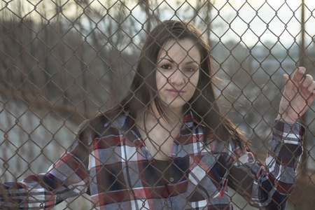 fense: A depress woman in front of a fense Stock Photo