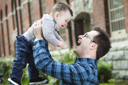 urban parenting: A Little baby and father having fun outdoors Stock Photo