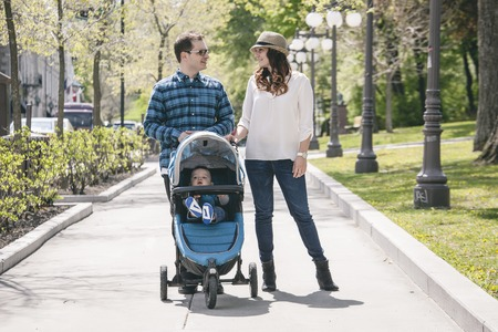A young family with baby strollers on city walk