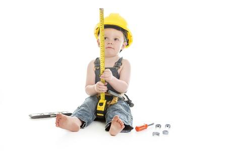 construction tools: Un retrato niño llevaba como carpintero sobre un fondo blanco aislado Foto de archivo