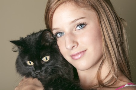 16s: A Young happy woman sitting on sofa with her cat at home Stock Photo