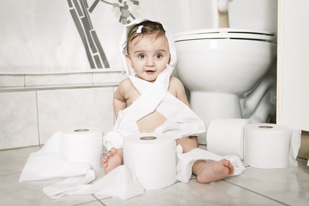 9 months: A Toddler ripping up toilet paper in bathroom Stock Photo