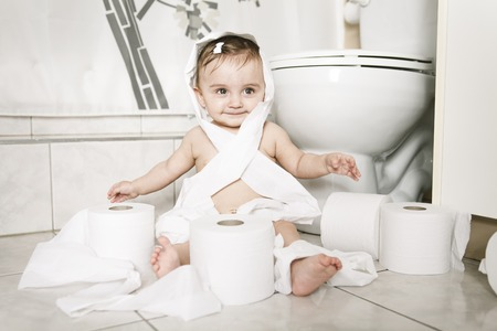 playful behaviour: A Toddler ripping up toilet paper in bathroom Stock Photo