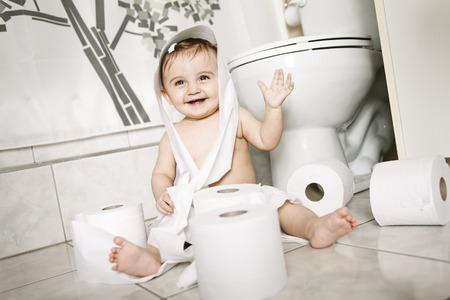 bebe sentado: Un ni�o de la rasgadura de papel higi�nico en el ba�o Foto de archivo
