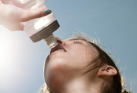 tomando agua: Una mujer deportiva joven bebiendo agua de una botella contra el cielo azul Foto de archivo