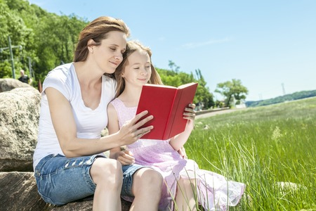 A Little girl with mother reading a book in a summer park