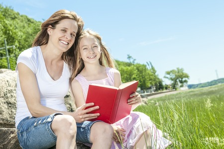 hobie: A Little girl with mother reading a book in a summer park