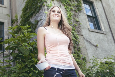 earbuds: A Teen girl listening to the music with earbuds from a smart phone on an urban background Stock Photo