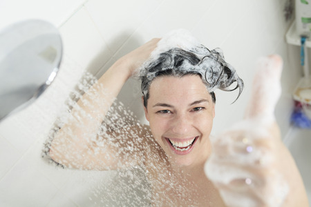 A positive thumb up woman with big smile on shower. Stock Photo