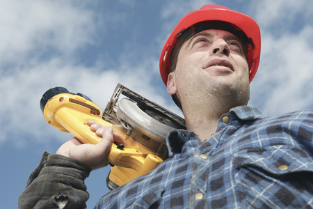 machinerie: A construction  men working outside holding a saw.