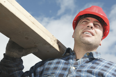 machinerie: A construction  men working outside holding a piece of wood. Stock Photo