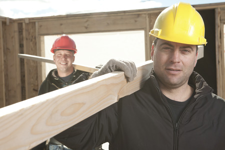 machinerie: Two construction  men working outside building a house with piece of wood.