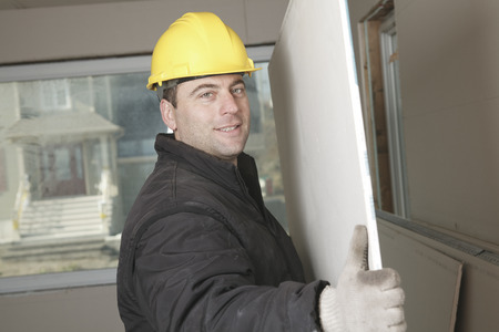 machinerie: A construction  men working posing a wall on a brand new bilding house.