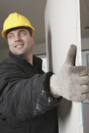 bilding: A construction  men working posing a wall on a brand new bilding house.