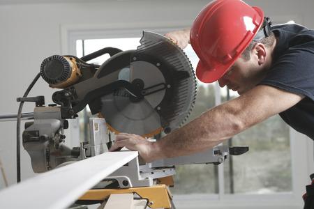 casco rojo: Un trabajador de la construcci�n con el casco rojo de trabajo con una sierra.