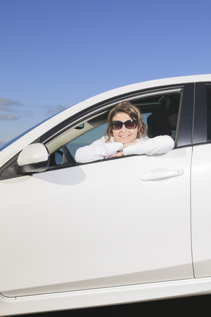 An happy woman with is white carn car. Imagens