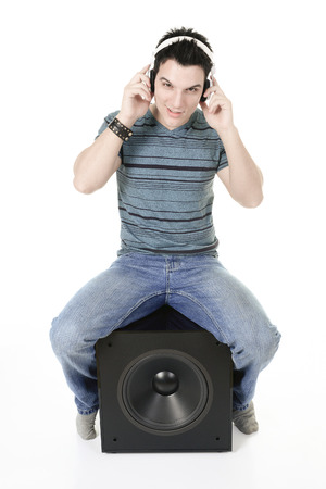 subwoofer: A Portrait of a smiling male sitting on a subwoofer with headphones.